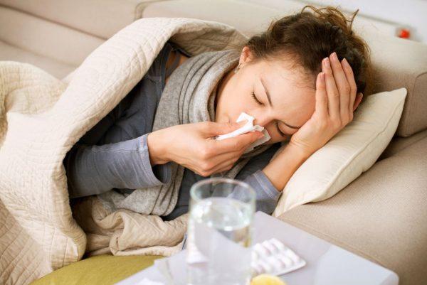 Женщина лежит в кровати, укутавшись шарфом и одеялом, вытирает нос платком и держится за голову