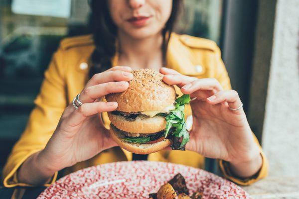девушка держит огромный гамбургер
