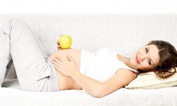 Беременная женщина с яблоком