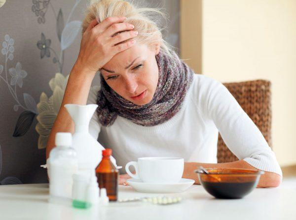 женщина сидит с обмотанной шарфом шеей, держась за голову