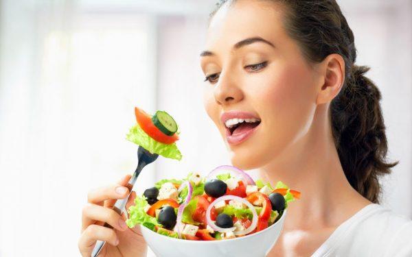 девушка подносит ко рту вилку с нанизанными кусочками овощей