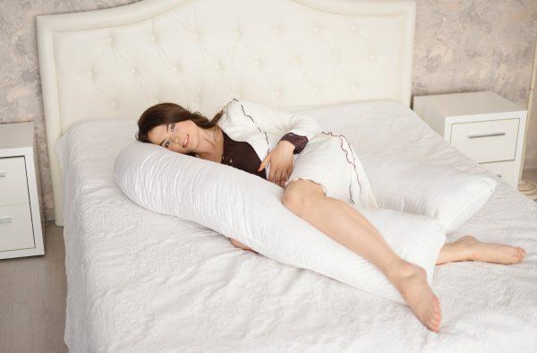 Женщина с подушкой для беременных на кровати